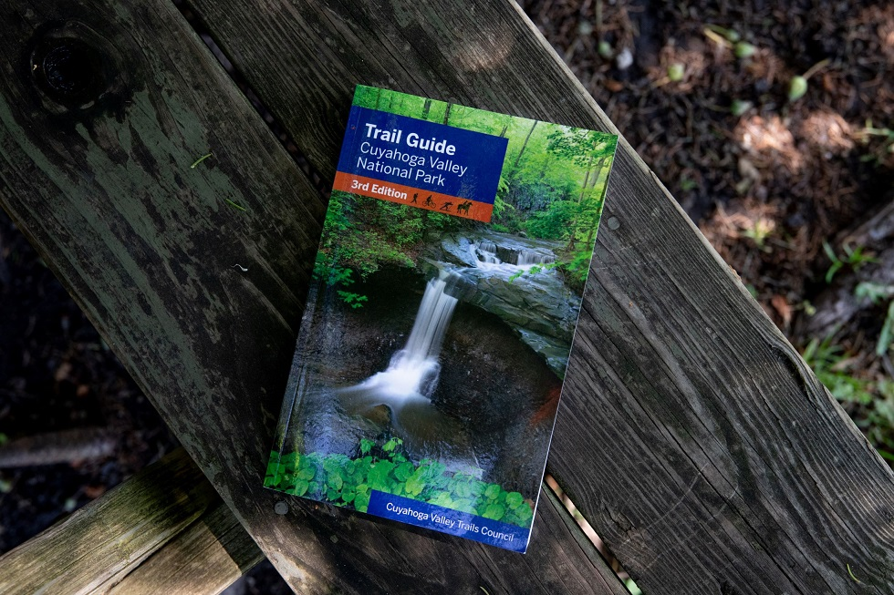 A trail guide of CVNP sits on a picnic bench.