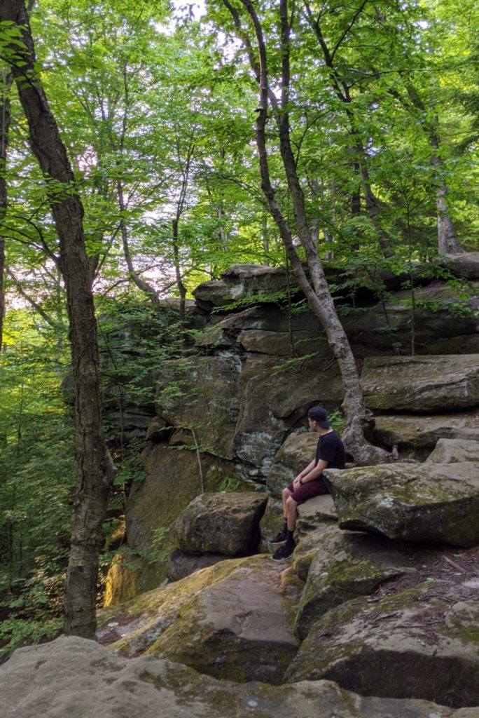 A person sits, looking away, on large rock formations in CVNP.