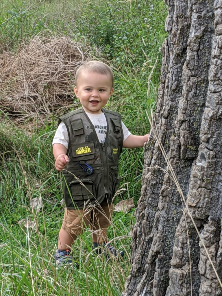 Little boy wearing Jr. Ranger vest plays peek-a-boo by tree