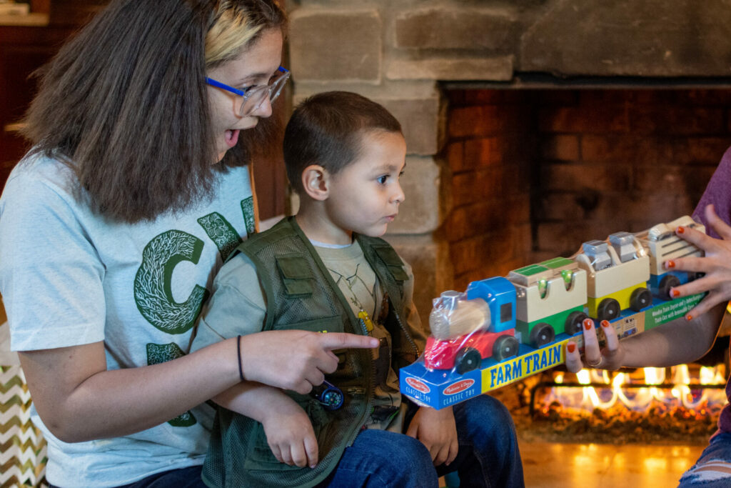Girl and boy look at toy train near fireplace