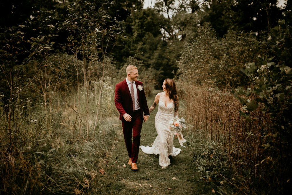 Newly married couple walks through a field