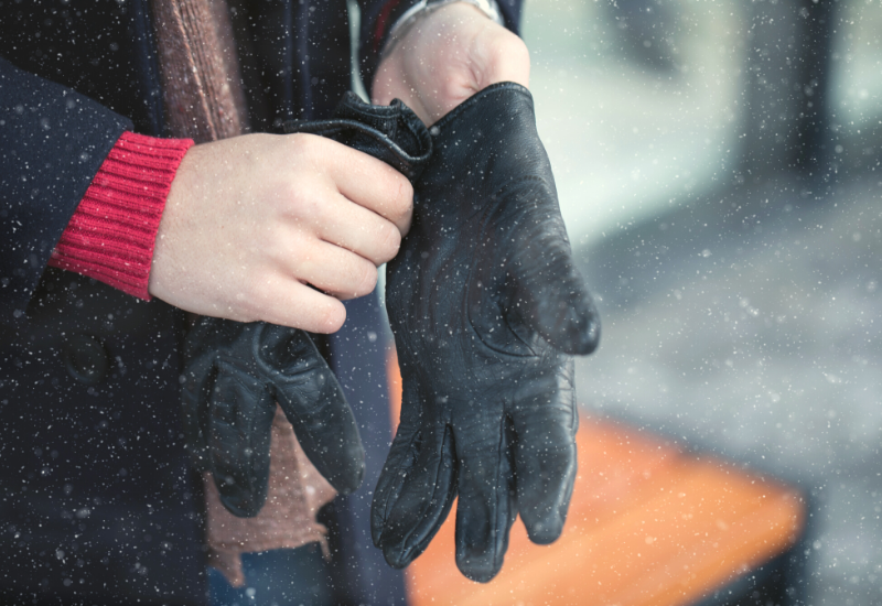Stock photo of man putting on winter gloves outside while it's snowing