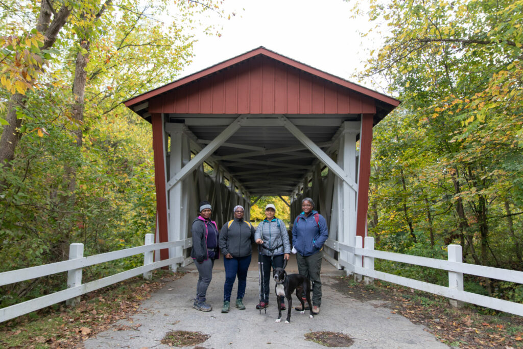 Conservancy staff photo of JOY group standing near covered bridge